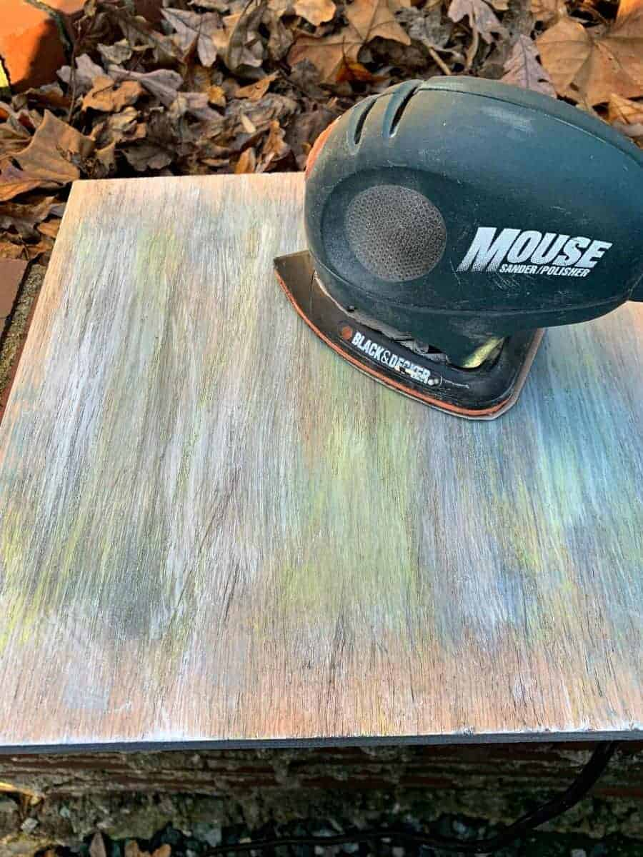 palm sander on top of painted piece of oak wood