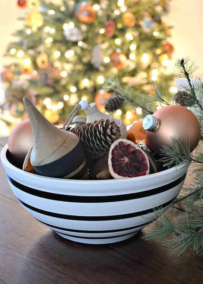 wooden and glass ornaments in a black and white striped bowl on a dining room table