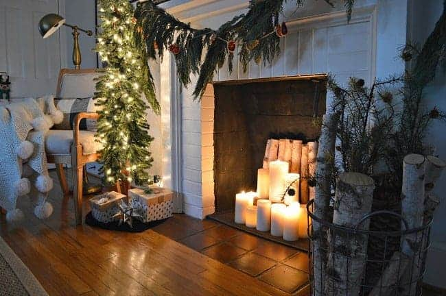 white brick fireplace with lighted candles in it and fresh greens hanging on it and a small, skinny lighted tree next to it