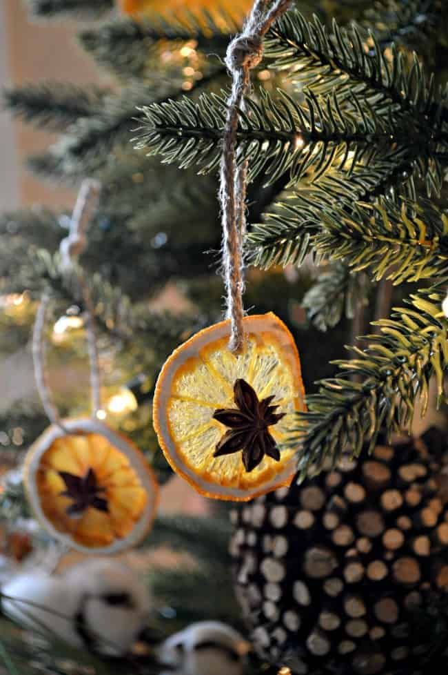 DIY dried orange slice ornaments hanging in a Christmas tree with a jute ribbon