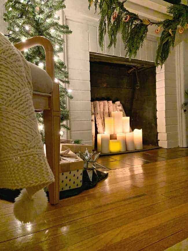 a white brick fireplace with lighted candles inside and greens hanging from the mantle