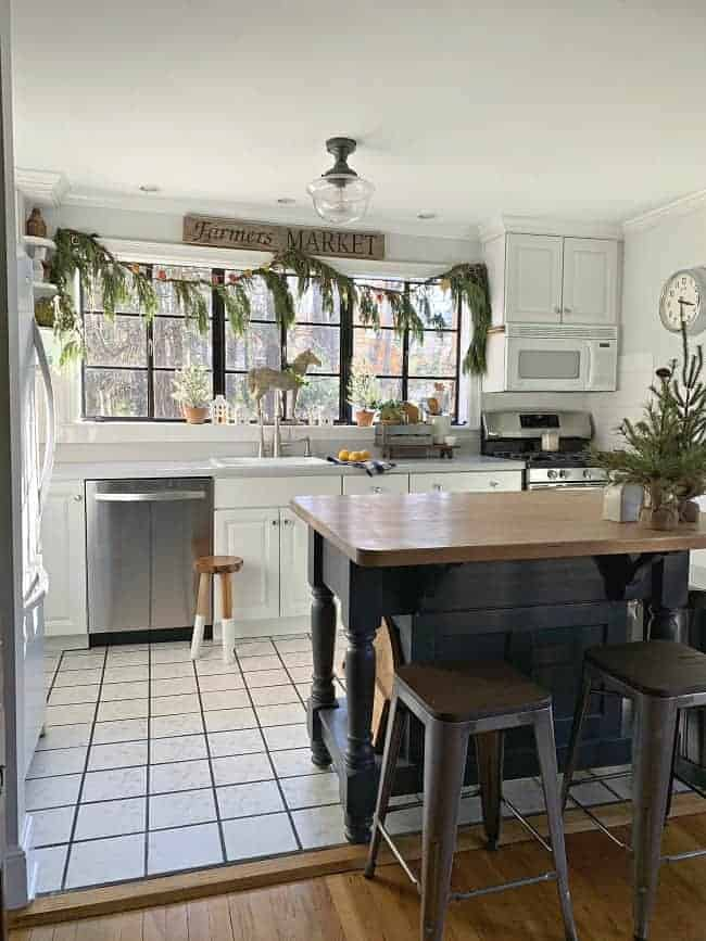aa view of a small white kitchen with fresh greens hanging on it