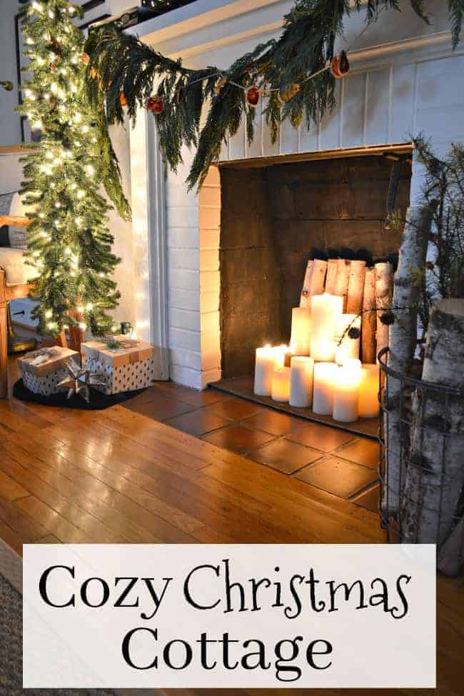 A cozy Christmas cottage with a white brick fireplace with lighted candles in it and fresh greens hanging on it. Plus a small, skinny lighted tree next to it