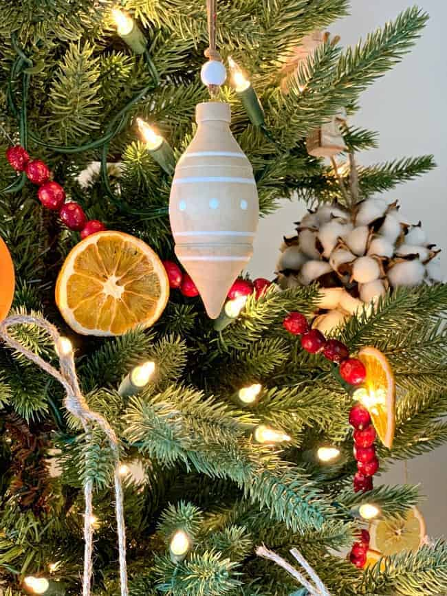 A DIY Christmas garland made with dried orange slices and cranberries and wooden ornament hanging on a tree