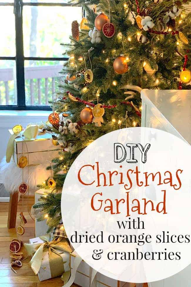 A DIY dried fruit garland made with dried orange slices and cranberries hanging on a nature-inspired Christmas tree