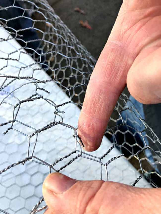 bending tabs in cut chicken wire to make DIY lighted chicken wire Christmas balls