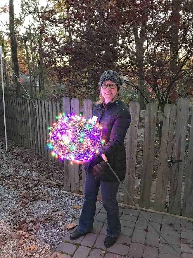 woman holding DIY Lighted Chicken Wire Christmas Ball