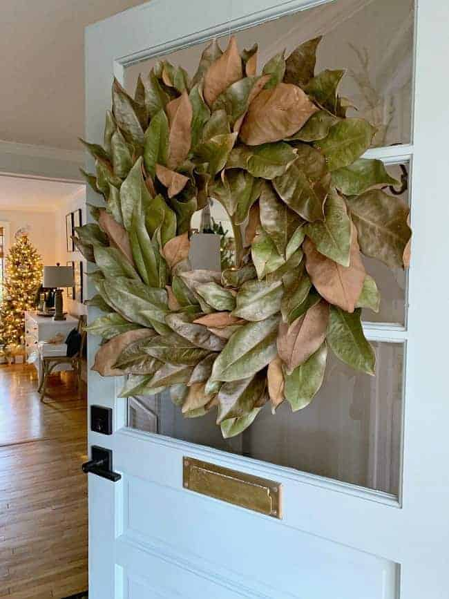 DIY Magnolia Wreath hanging on an open front door with Christmas tree in the background