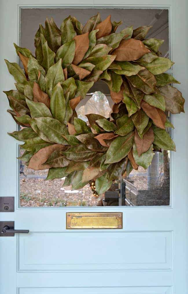 DIY magnolia wreath hanging on a blue front door