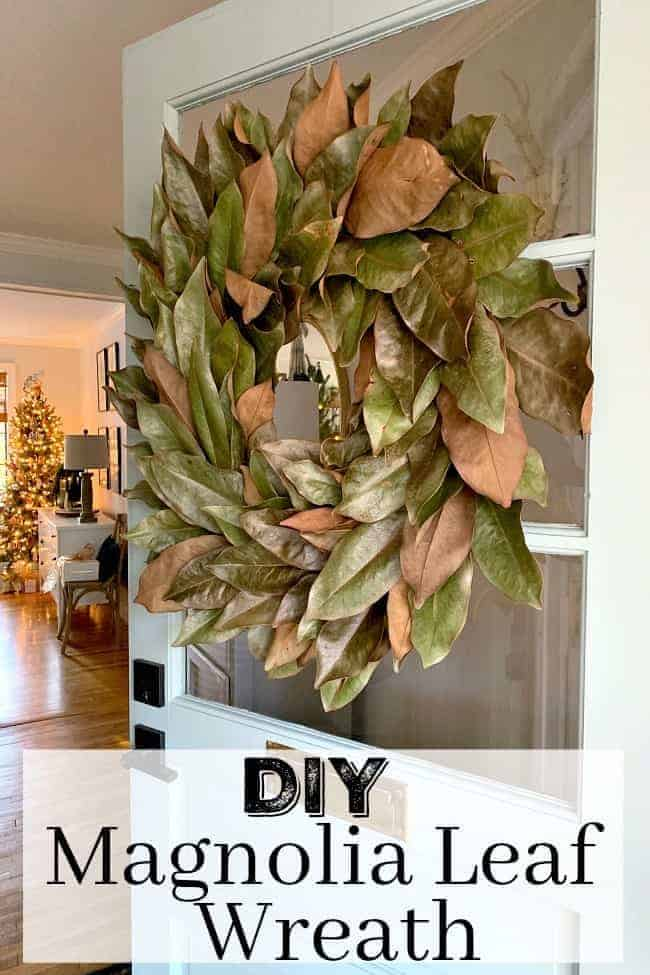 DIY Magnolia Wreath hanging on an open front door with Christmas tree in the background, and a large graphic