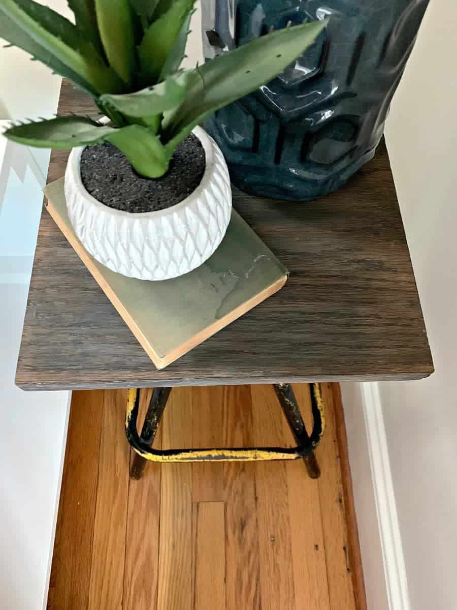 top view of DIY nightstand with a blue lamp and potted plant next to platform bed