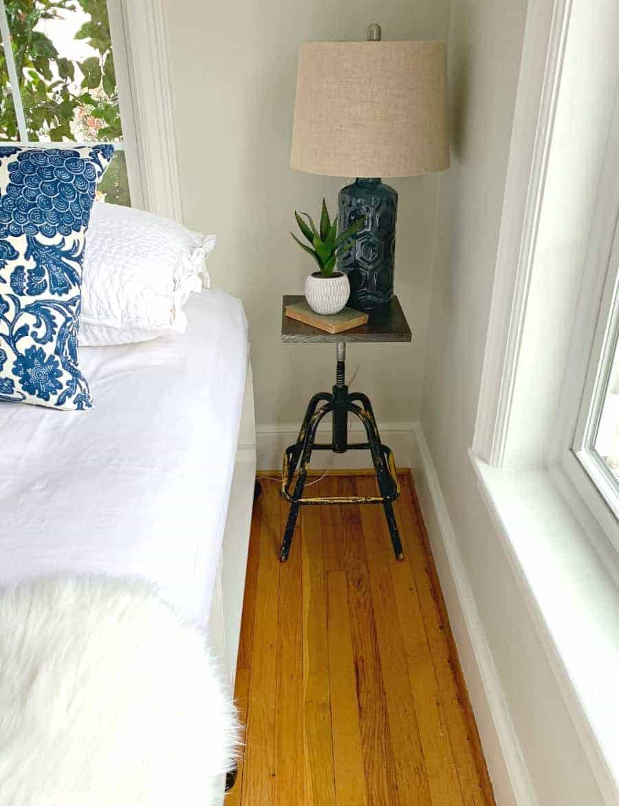 DIY nightstand next to bed with blue lamp, book and plant on top