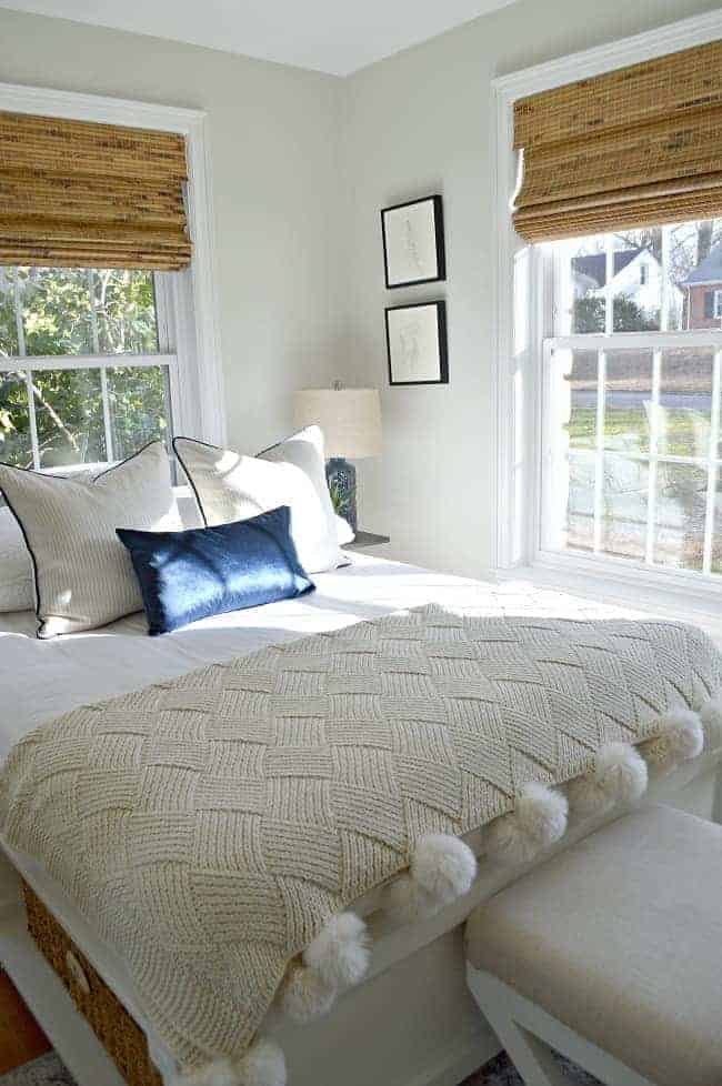 platform bed with textured throw and woven shades in window for guest bedroom makeover