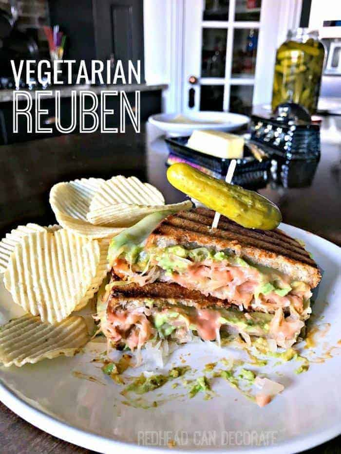 vegetarian reuben on plate with pickle and chips