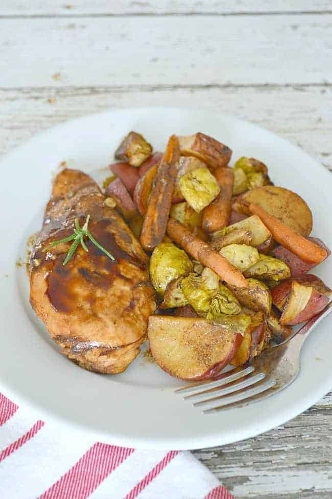 One pan balsamic chicken and roasted vegetables on white plate with red and white napkin