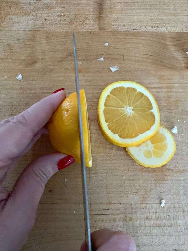 slicing oranges on a butcher block countertop