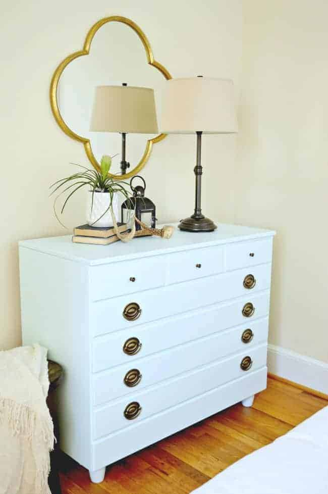 icy blue paint on Goodwill dresser in corner of bedroom with lamp and plants on it