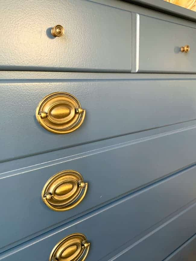 side view of navy dresser with antique brass hardware