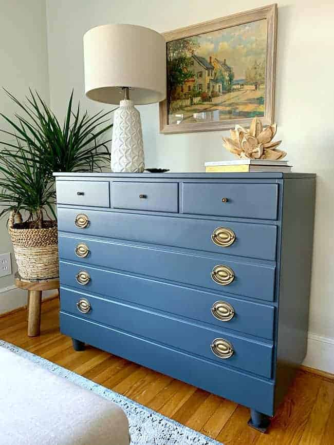 DIY dresser makeover in navy with white lamp and watercolor painting hanging above it