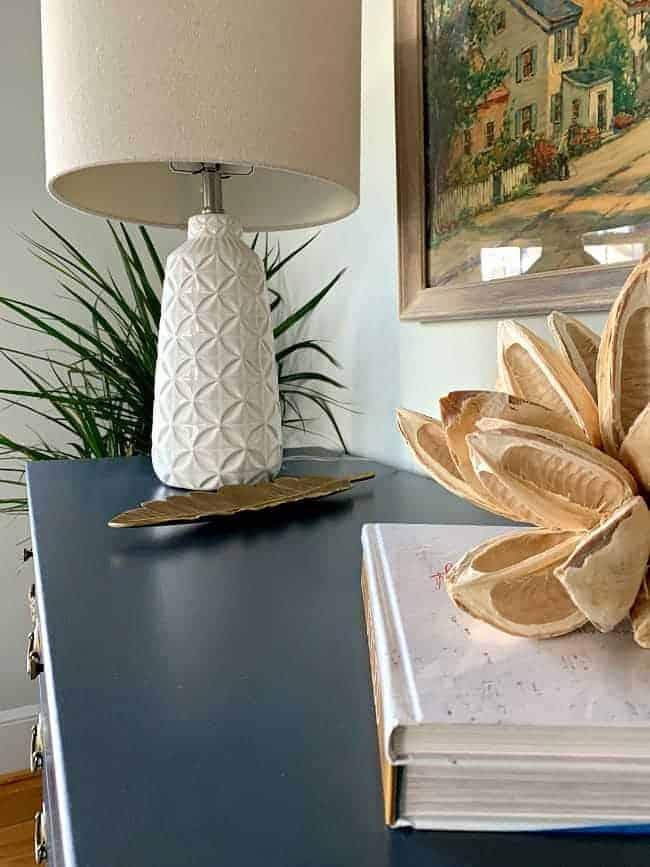 top of navy dresser with lamp, books and seed pod on top