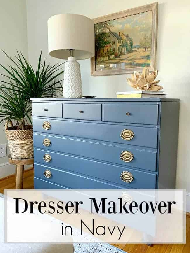 DIY old dresser makeover in navy with white lamp, seed pod and watercolor painting hanging above it