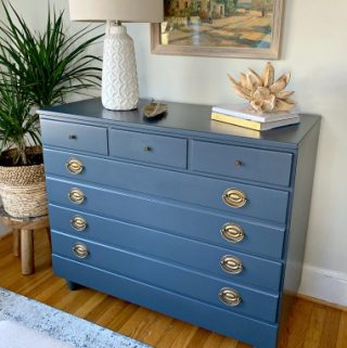 navy painted dresser in guest bedroom with lamp and other decor on top
