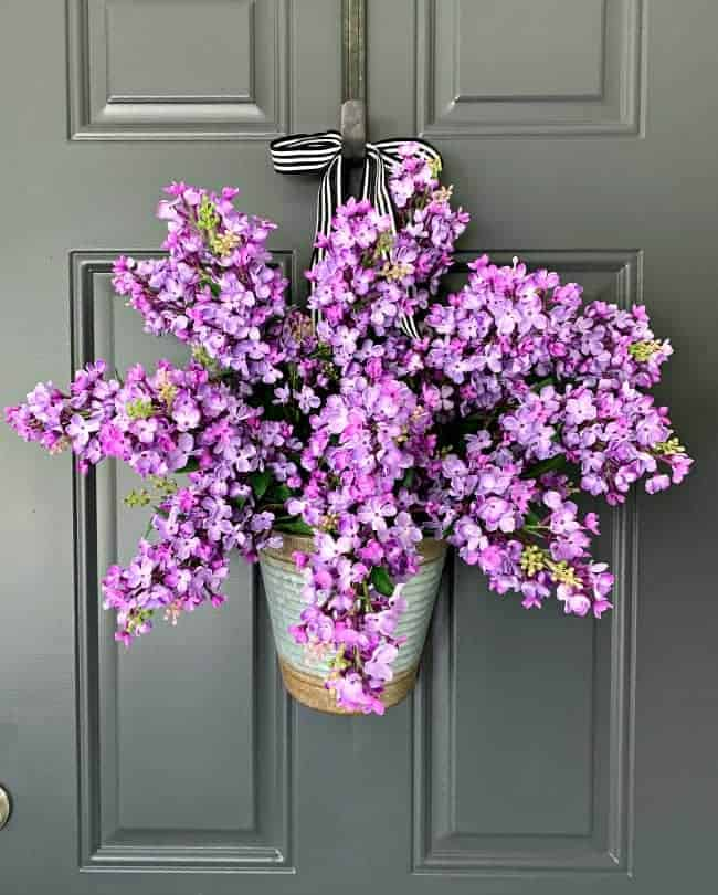 easy DIY spring wreath with lilacs hanging on charcoal painted door