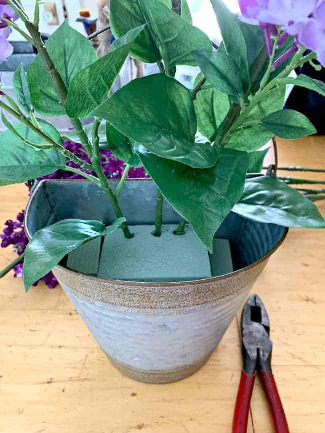 inserting faux stems into floral foam in rusty bucket