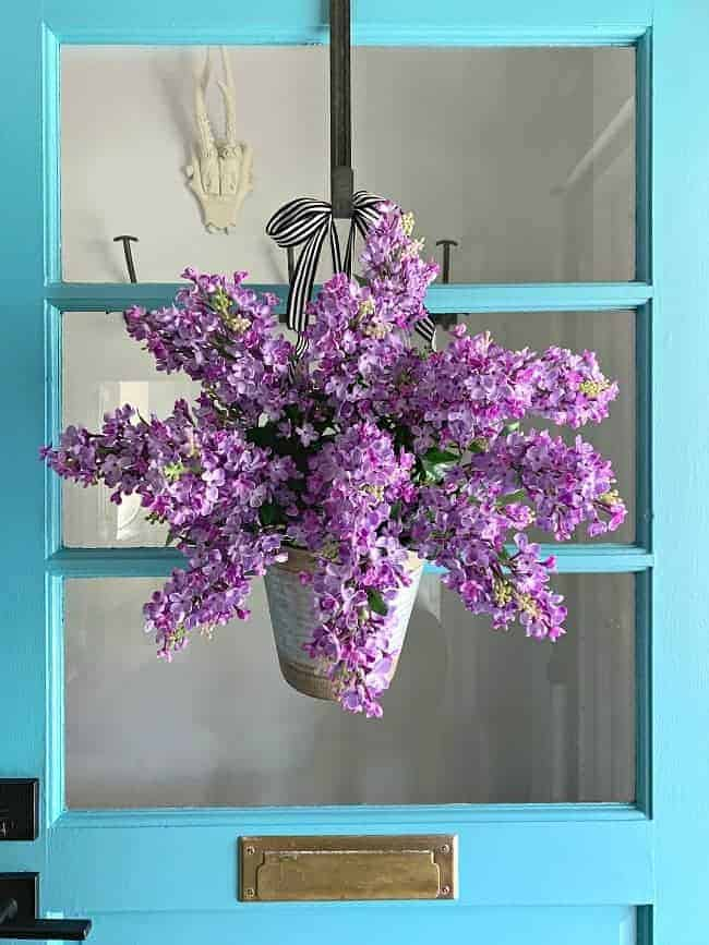 bucket filled with faux lilacs hanging on turquoise front door