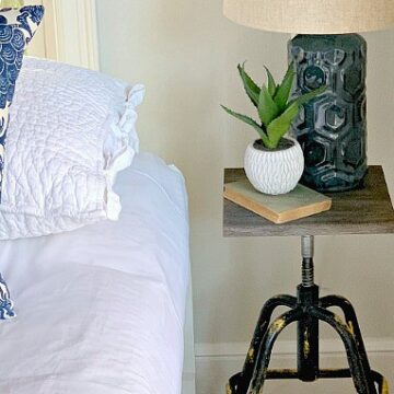 A small nightstand with a lamp and plant