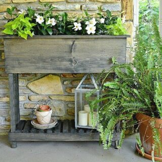 finished DIY wood raised planter box with legs with flowers planted in it and old pots on bottom shelf