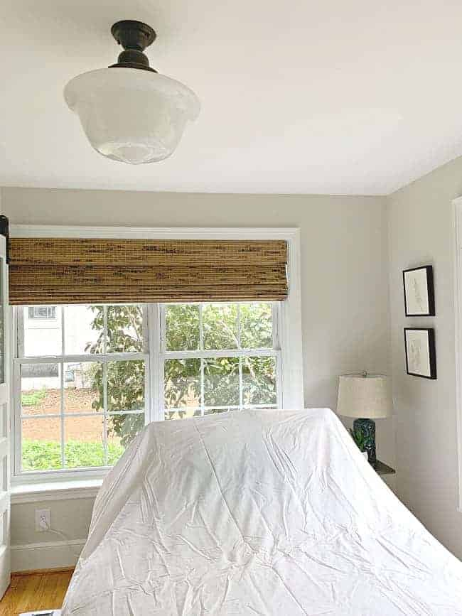 off-center schoolhouse ceiling light fixture in a guest bedroom