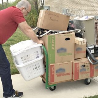 man pushing cart filled with moving boxes