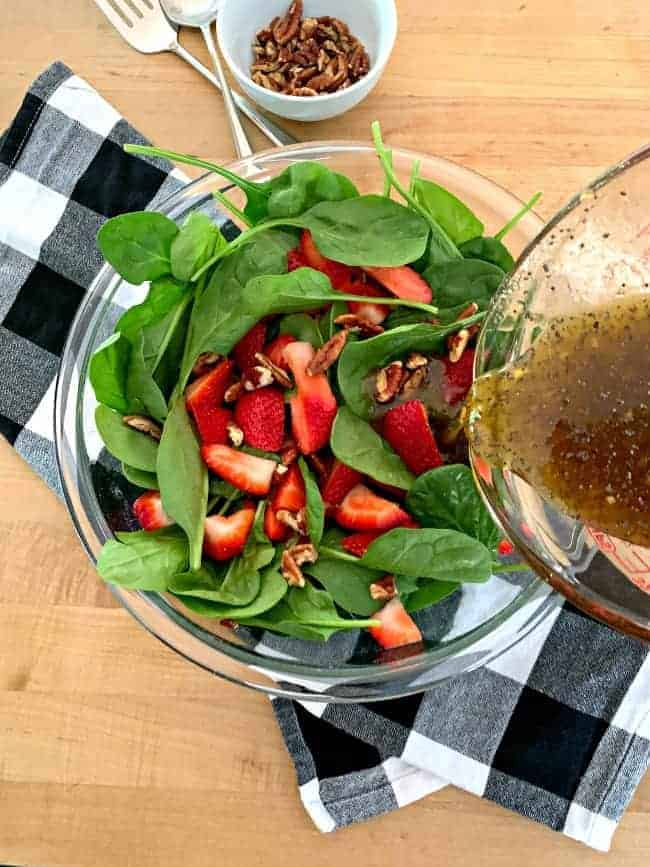 pouring poppy seed dressing over a spinach strawberry salad with chopped pecans