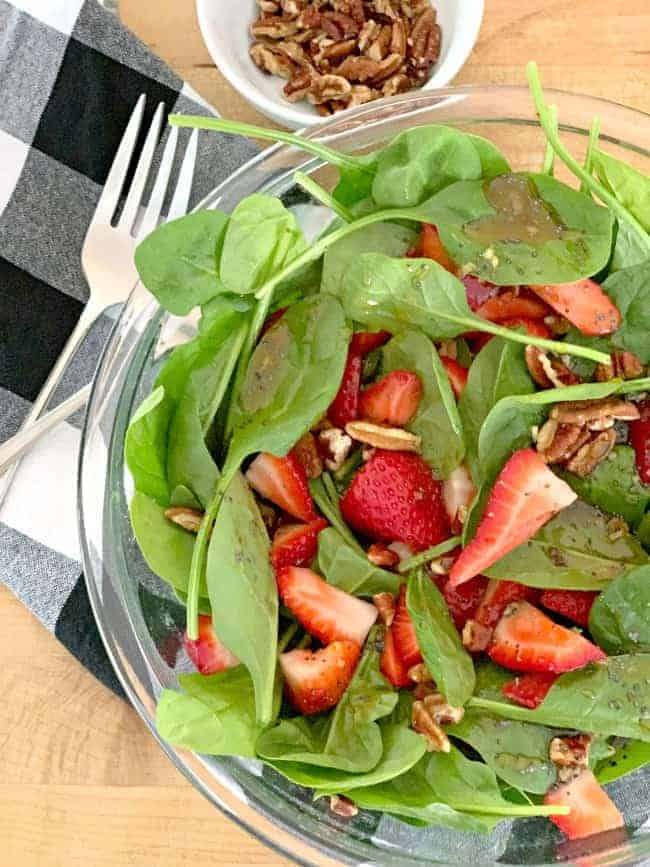 top view of a spinach strawberry salad with poppy seed dressing and a small bowl of chopped pecans