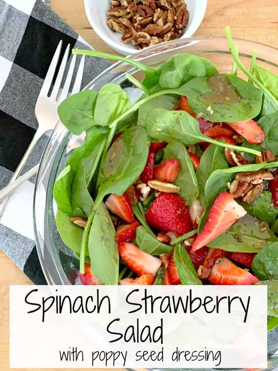 top view of spinach strawberry salad with a small bowl of chopped pecans next to it, plus a large graphic