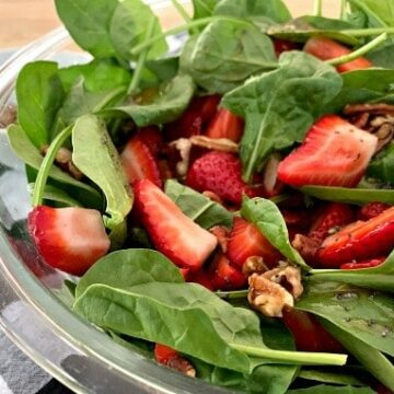 A bowl of salad, with Spinach and Strawberry