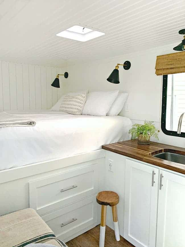 view of big white bed and kitchen cabinet in tiny RV