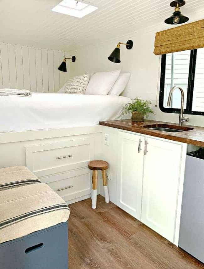 inside view of RV renovation with a big white bed, kitchen sink and counter and navy wood storage stools