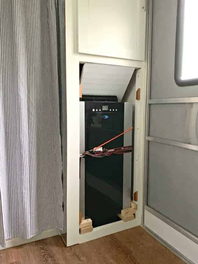 a portable a/c unit built in to a cabinet with straps around it to keep it secure