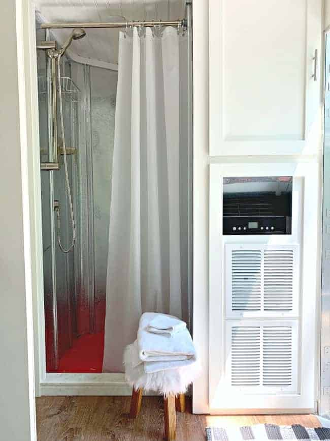 view of metal walls on shower, and shower curtain liner, along with a cabinet next to the shower