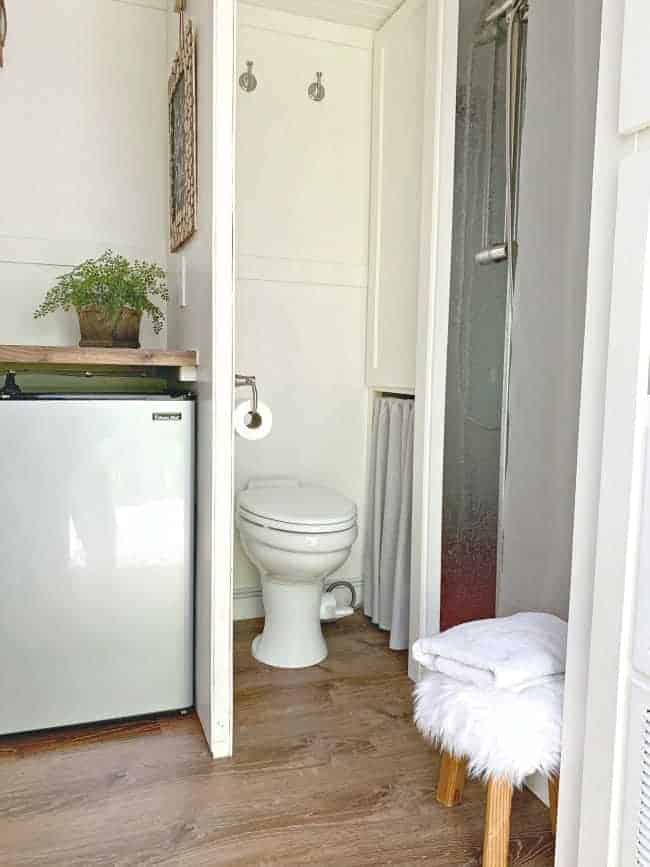view of a tiny RV bathroom with porcelain toilet and bathroom wall with mini fridge on the opposite side