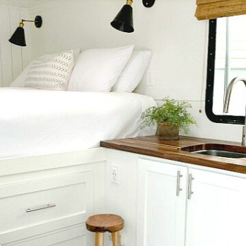 A kitchen with a sink and a bed in a cargo trailer conversion