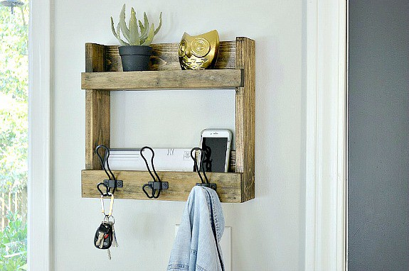 DIY coat rack with storage shelves hanging on wall with plant, owl and keys hanging on it