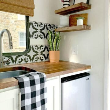 tiny RV kitchen with removable wallpaper backsplash, plant in corner and black and white towel on sink