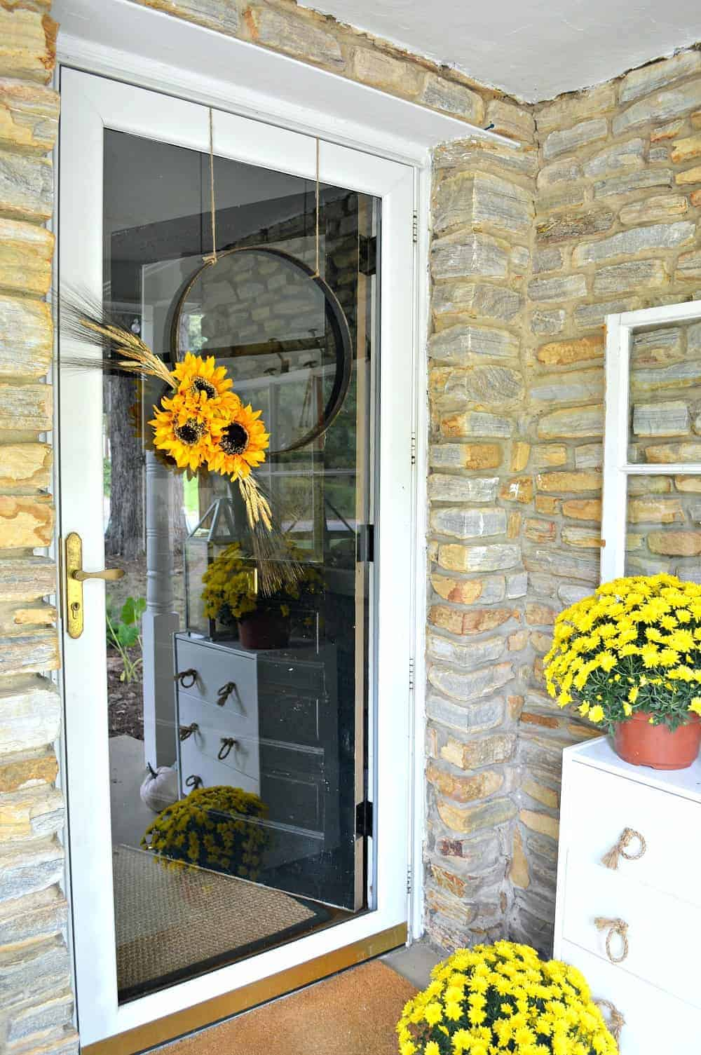 A simple DIY fall front door wreath made with an embroidery hoop hanging on a front door