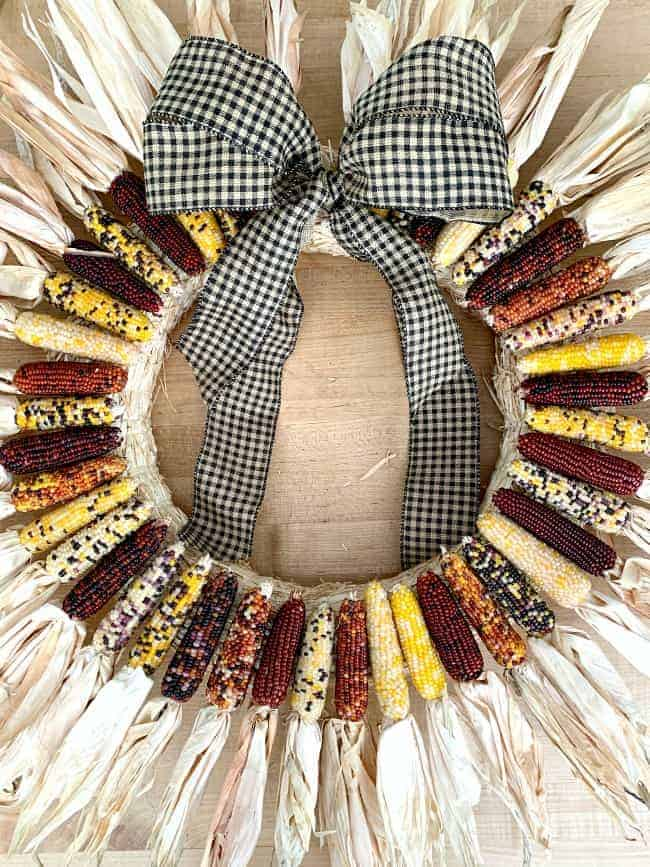 mini Indian corn wreath with a large bow laying on a butcher block