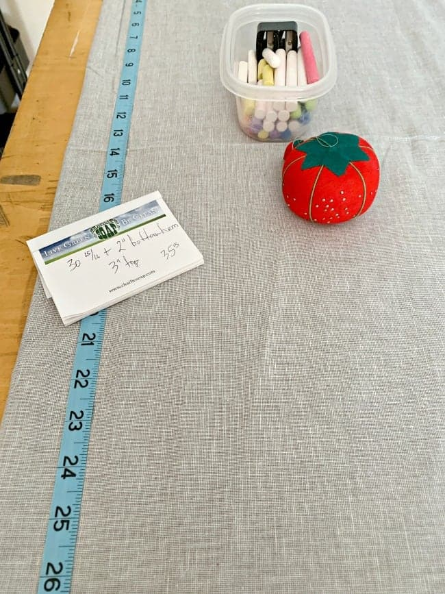 gray fabric for no sew curtain with tape measure, straight pins and bowl of chalk