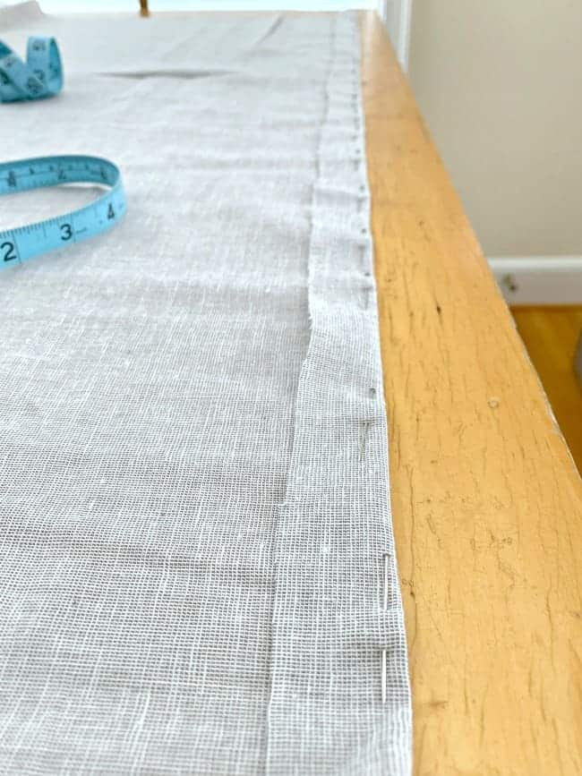 "gray fabric on table pinned with a 1"" hem"