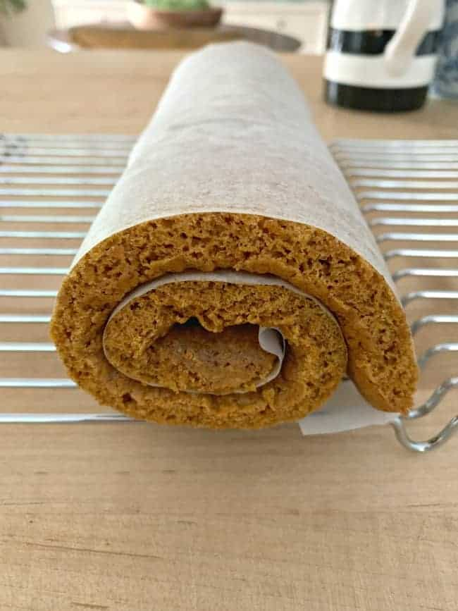 pumpkin cake rolled up in parchment paper cooling on baking rack